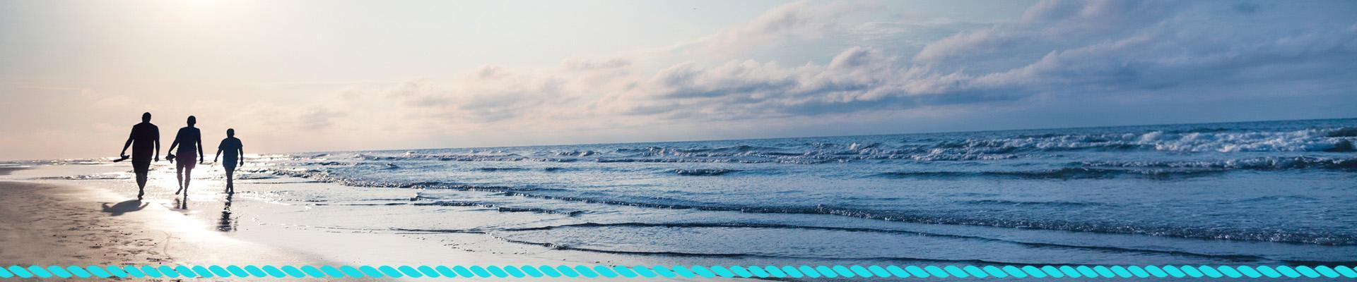 Ludzie spacerujący brzegiem morza